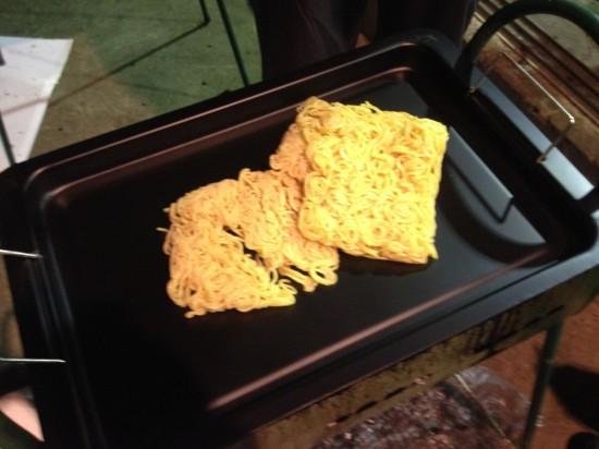 鉄板、焼きそば用アルミプレートをBBQグリルに乗せ、サラダオイルを引いた後に、そば玉を鉄板の上に