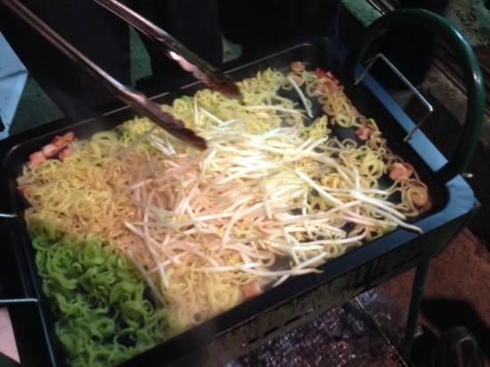 もやしなどの野菜、肉、ソーセージなどを加えて炒めます。